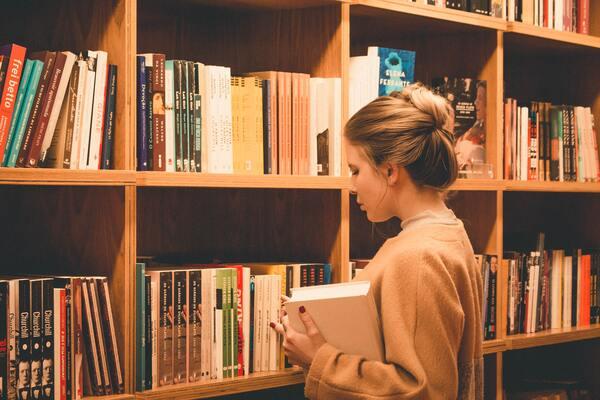 A imagem contém uma estudante escolhendo livros em uma estante de biblioteca.