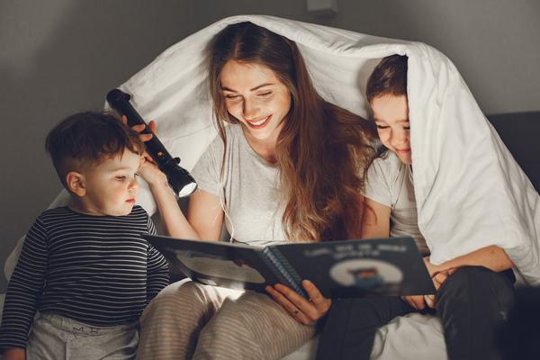 A imagem contém uma mulher seguindo as dicas de bem estar infantil e lendo para suas crianças.