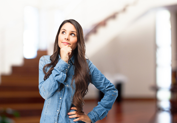 A imagem contém uma jovem apoiando a mão no queixo com expressão de dúvida sobre qual a sua vocação.