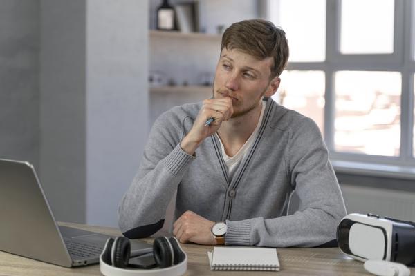 A imagem contém um jovem sentado sobre uma mesa, com o olhar reflexivo sobre qual sua vocação.