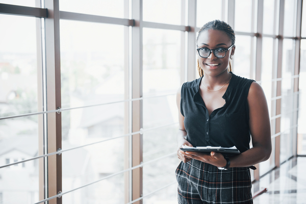 A imagem contém uma jovem administradora que soube o que faz uma pessoa formada em Administração antes mesmo de começar o curso. Ela se mostra feliz e segura um tablet.
