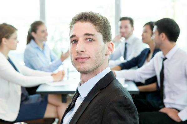 A imagem contém um jovem administrador que sabe o que faz uma pessoa formada em Administração, sendo uma das funções liderar uma equipe.