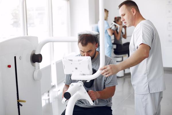 A imagem contém um especialista em Medicina Esportiva fazendo tratamento em máquina com um atleta.