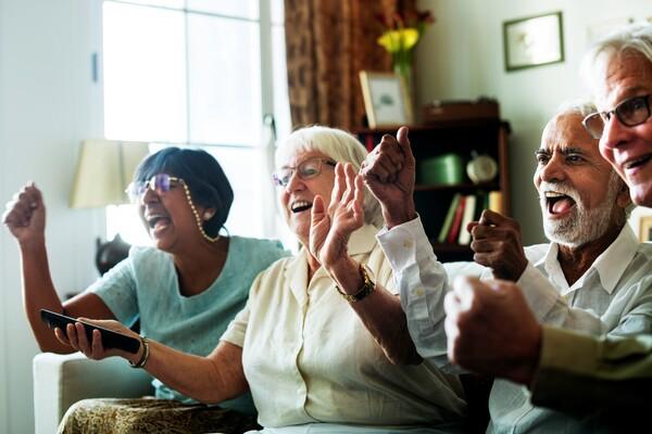 A imagem contém duas senhoras e dois senhores sentados num sofá com expressão de comemoração.