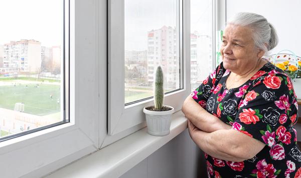 A imagem contém uma senhora olhando sorridente para a paisagem além de sua janela, feliz pela sua qualidade de vida, elemento que influencia no envelhecimento populacional.