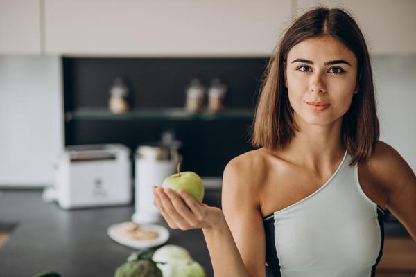 A imagem contém uma profissional da nutrição esportiva segurando uma maçã-verde.