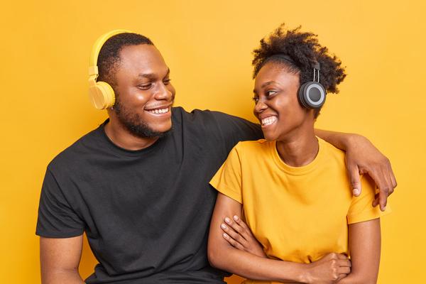 A imagem contém dois jovens abraçados e sorridentes dando apoio um ao outro, uma ação importante para a campanha Setembro Amarelo.