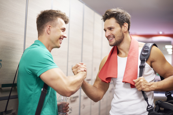 A imagem contém um profissional da nutrição esportiva dando um aperto de mão em seu aluno.