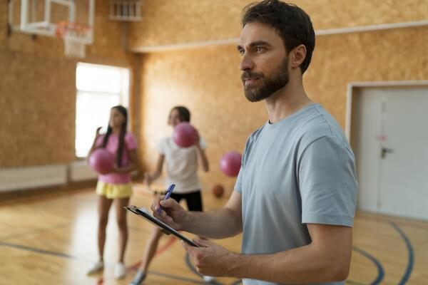 A imagem contém um profissional que fez licenciatura em Educação Física atuando em uma escola com sua turma de alunos.